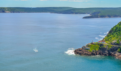 Boats motor past Fort Amherst.  Rugged coastline and Atlantic ocean. Warm summer day in August, speeding boat passes by, appears slow in the vastness.