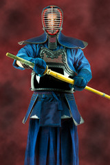 Kendo - Kendoka in full armor and bamboo sword. Studio shot.