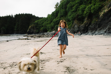 Young girl being pulled along by pet dog