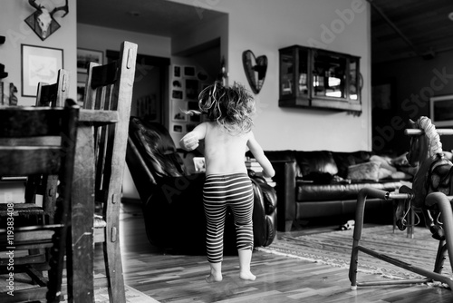 0103157f Young girl jumping in living room, black and white