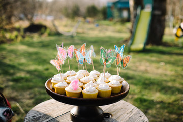 Cupcakes on a cake stand with decorative butterflies