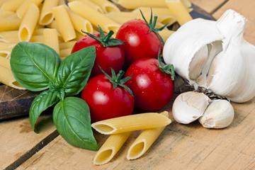pasta, tomato and garlic on wood background