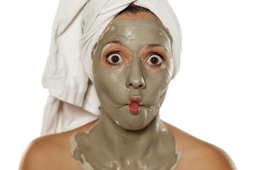 young silly woman with a towel on her head applied a mud mask on her face making sh facefi