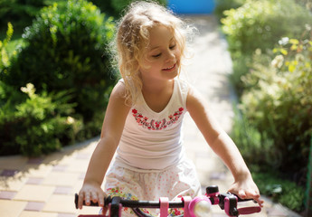 Beautiful little girl on a bicycle in the park, summer outdoor