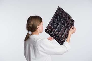 Female doctor examining an x-ray picture, back-view