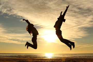 Couple or friends jumping on the beach at sunset