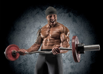 Handsome power athletic man bodybuilder doing exercises with bar