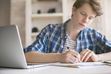 Young man writing essay