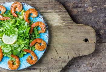 Seafood shrimp prawns lettuce salad on blue plate. Top view