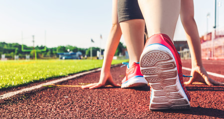 Female athlete on the starting line of a stadium track