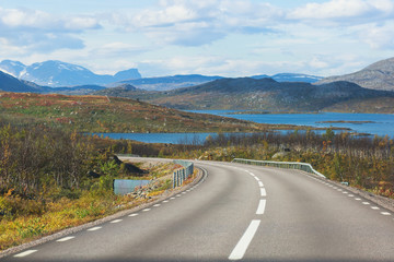 Beautiful vibrant fall autumn landscape of national park near border of Finland, Sweden and Norway, with mountains, camping place, road and forest