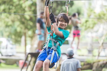 active brave boy enjoying outbound climbing at adventure park on