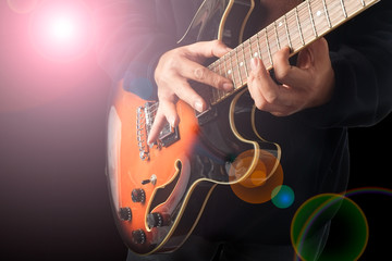 A man is playing guitar with lighting effect.