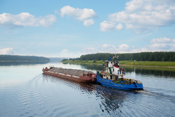 Tugboat moves barge on the Volga river