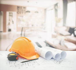 architectural blueprint with safety helmet and tools over modern living corner next to the dining room