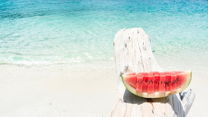 Slice of watermelon on timber against beach background.
