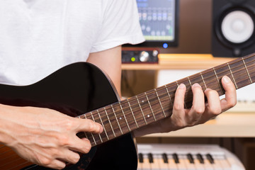 musician hands playing acoustic guitar in recording studio