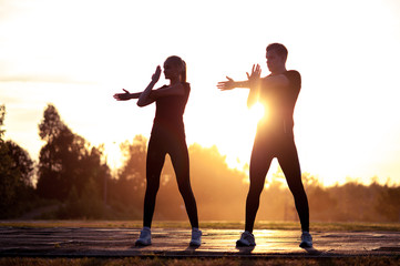 Silhouettes of young adults exercising at sunset