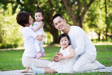 Young happy Asian family enjoying a sunny day at the park.