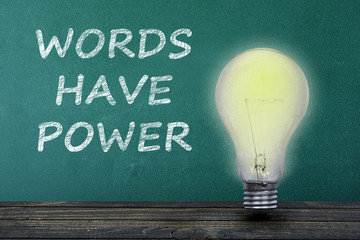 Words have power text and light bulb on table