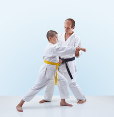 On a light background with black belt a master teaches athlete