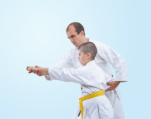 The learner with a yellow belt karate coach corrects