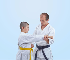 With black belt athlete is teaching athlete with a yellow belt