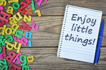 Enjoy little things text on notepad and magnetic letters
