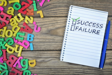 Success text on notepad and magnetic letters