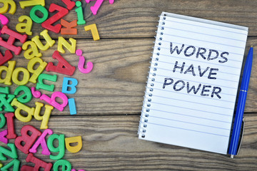 Words have power text on notepad and magnetic letters
