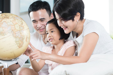 Asian parents exploring the globe with their child.