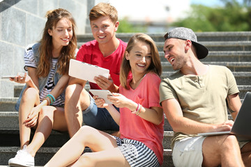 Young people with gadgets on stairs