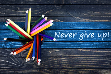 Never give up text painted and group of pencils
