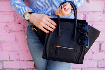 Close up black leather bag in hand of fashion woman. Wall mural