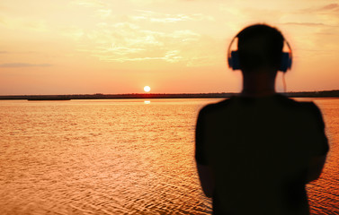Silhouette of man with headphones on sunset sky background