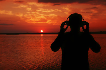 Photo sur Plexiglas Rouge traffic Silhouette of man with headphones on sunset sky background