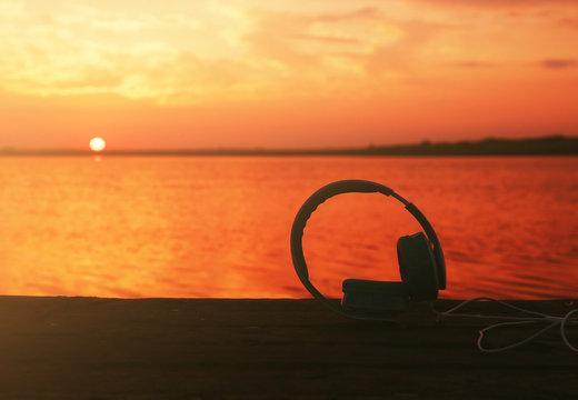 Headphones on sunset sky background