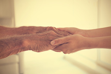 Old male and young female hands, closeup