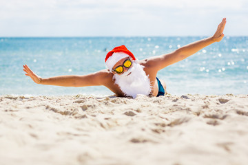 Pretty Santa Claus in sunglasses on the beach with ocean views