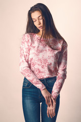 Beautiful young woman. Girl in casual clothes on a light background. Girl in jeans. Sexy girl. Toning of vintage style.