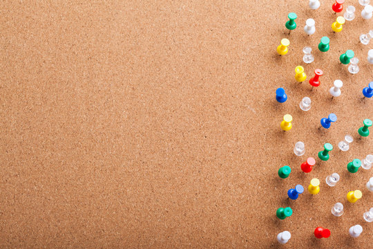 Group of thumbtacks pinned on corkboard