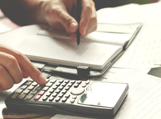 savings, finances, economy and home concept - close up of man with calculator counting making notes at home, hand is writes in a notebook with books, soft focus.