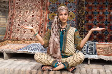 The girl - a Muslim woman on the background of silk handmade carpets