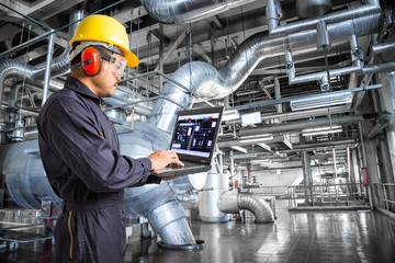 Engineer using laptop computer in the factory