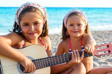 Children having fun with guitar on beach.