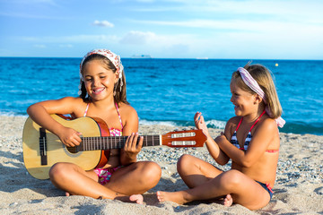 Little girls singing with guitar on beach.