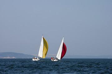 Sailing boats racing under color sails