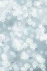 A blue grey bright sparkly abstract background of retro tinted Christmas holiday bokeh lights.