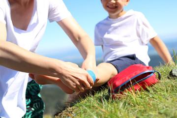 Obraz Wypadek na górskim szlaku. Dziecko skręciło nogę w kostce podczas górskiej wycieczki. Opatrywanie złamanej nogi. - fototapety do salonu