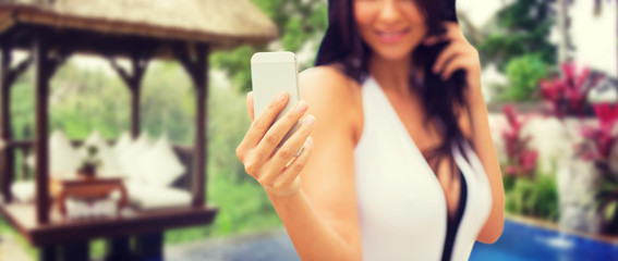 woman taking selfie with smartphone over bungalow